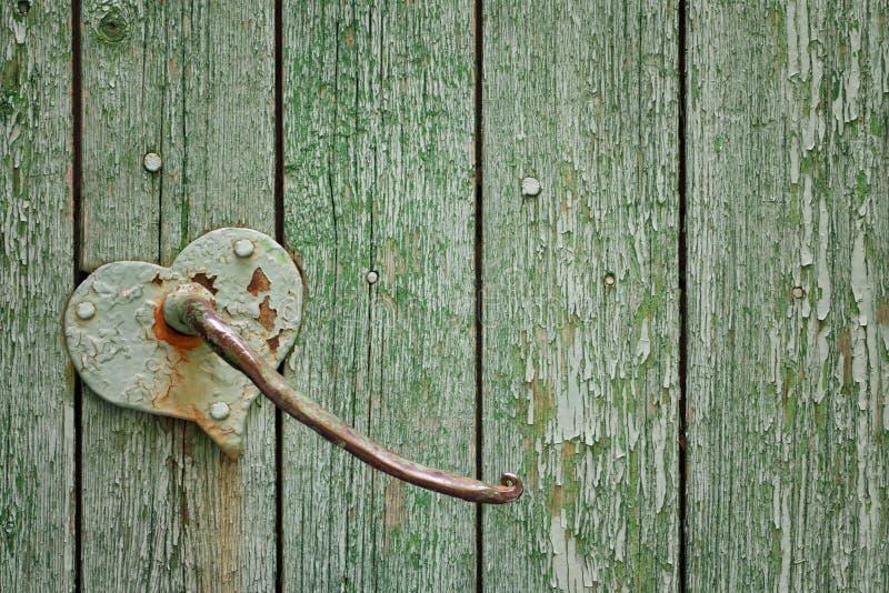 Green verticallyarranged vintage planks with heart shape door handle. Texture. Background stock images