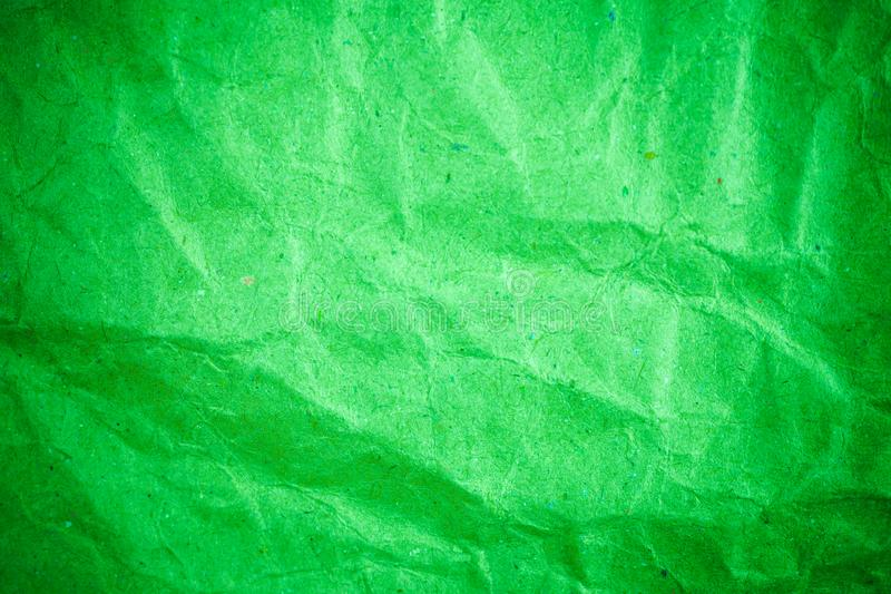 Green vignette crumpled paper. Abstract, ancient, backdrop, background, blank, card, cardboard, color, crease, creased, damaged, design, detail, dirty, effect royalty free stock photography