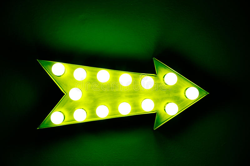 Green vintage bright and colorful illuminated display arrow sign. With light bulbs against a green dark background stock image