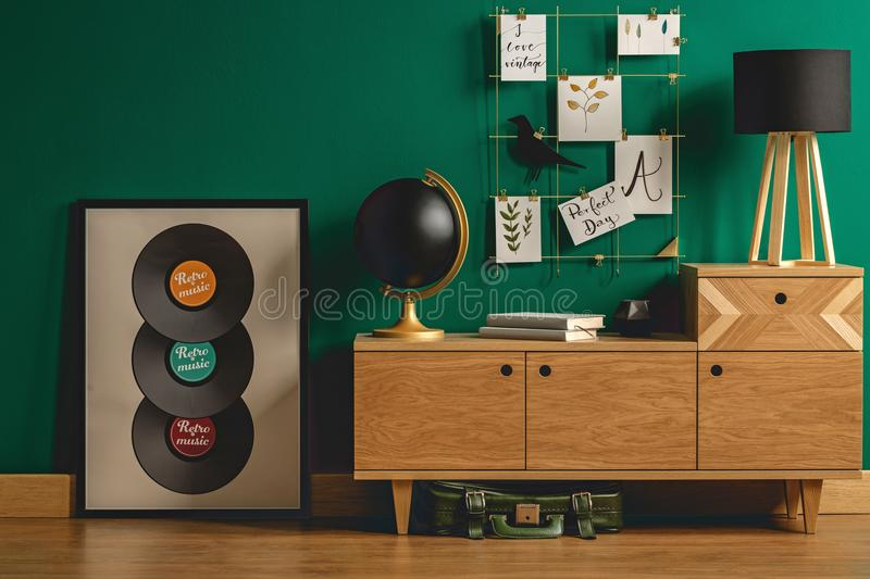 Green bag under retro dresser. Green vintage leather bag under a retro dresser with hipster decorations and a tripod desk lamp in a student`s bedroom interior royalty free stock photography