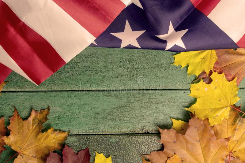 Green vintage wooden background covered with american flag and autumn leaves, copy space.  stock photos
