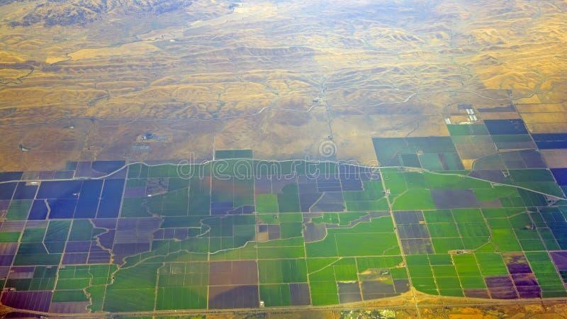 Green vs Gobi desert. The green farm land and yellow Gobi desert, Opposites attract of landform royalty free stock images