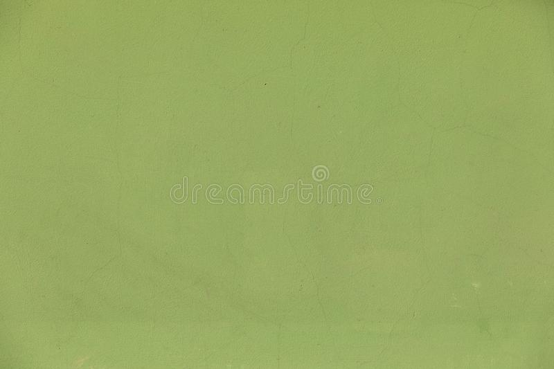 Green wall background with cracks on plaster surface. Green  lime wall background with cracks on plaster surface. Copy space stock image