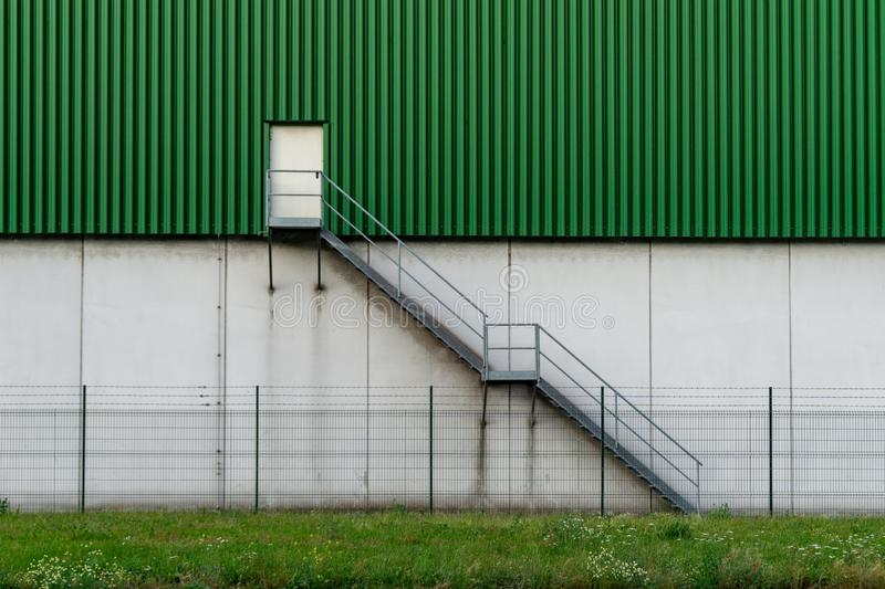 Green wall of modern building - stairway and door - concept image stock image