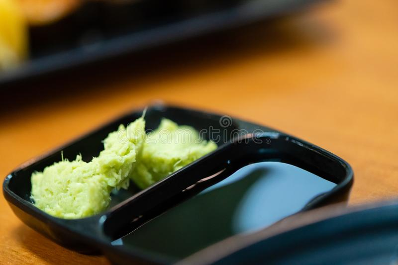 Green wasabi.traditional japanese local garnish for sashimi.wasabi for delicious seafood sushi on black plate.wasabi for customer. At japanese restaurant and stock images