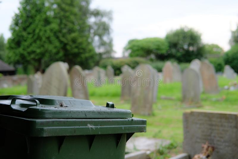 Green waste wheelie bin seen located by the side of an old cemetery. The green waste bin is used for visitors to discard dead flowers from the mass of royalty free stock photo