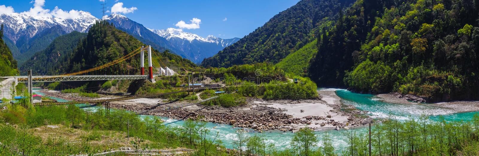 Panoramic view of snow mountain , clear green river landscape of valley. Green water , snow mountain , white clouds , highway bridge ,landscape of river valley royalty free stock photos