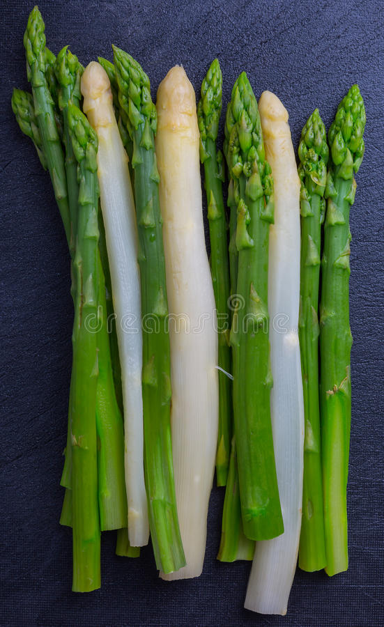 Green and white asparagus on black background royalty free stock photo