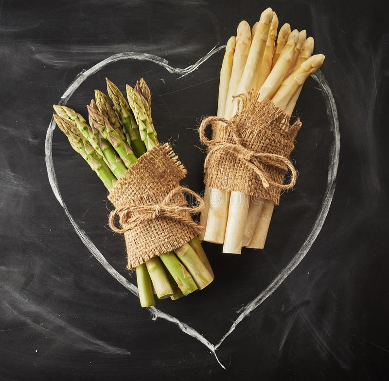 Green and white asparagus on a hand drawn heart. Fresh bundles green and white asparagus tied with hessian on a hand drawn heart in chalk on slate conceptual of royalty free stock photo