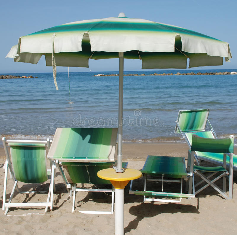 Green and White Beach Umbrella. S and deckchairs on a beach on a sunny summers day royalty free stock image