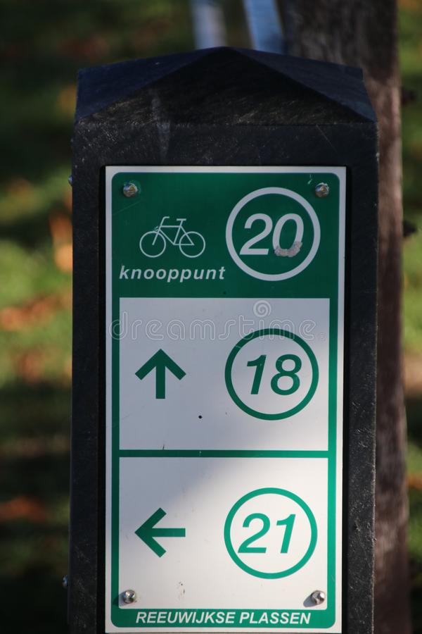 Green and white direction signs to the nearest node in the network for cyclist in the Netherlands. stock photo