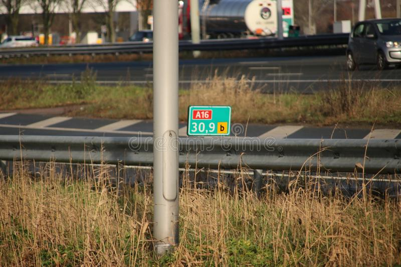 Green and white distance sign in kilometers at a shoulder along motorway A16 at Zwijndrecht in the Netherlands. stock photo