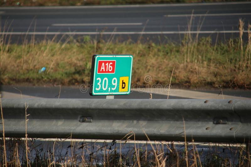Green and white distance sign in kilometers at a shoulder along motorway A16 at Zwijndrecht in the Netherlands. royalty free stock photography