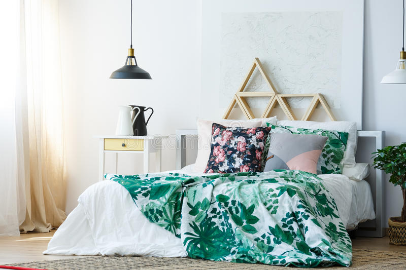 Green and white floral bedclothes. In stylish bedroom royalty free stock images