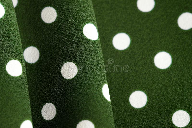 Green and white polka dot textile. Abstract background. Green and white polka dot textile close up. Abstract background stock illustration