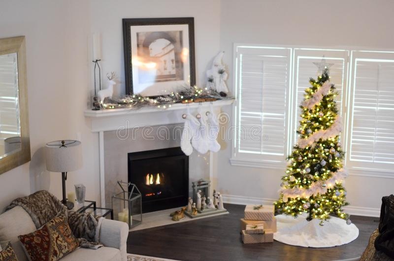 Green and White Pre-lit Pine Tree Near Fireplace Inside Well Lit Room royalty free stock photography