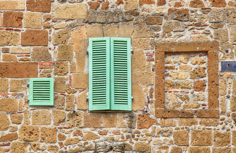 Green window shutters on old stone textured wall, Italy stock photography