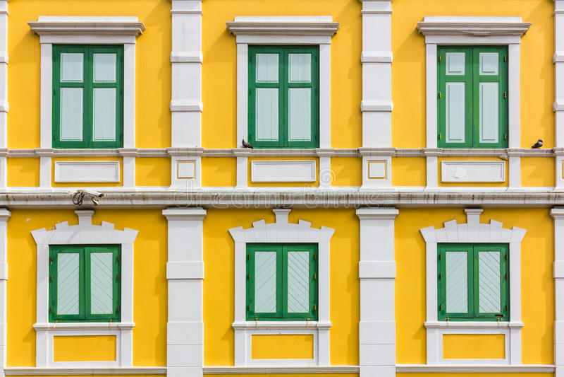 Green window on yellow wall royalty free stock image