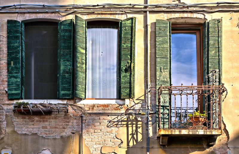 Green windows and balcony with old building facade and brick texture in Venice, Italy. Green windows and door balcony with old building facade, glass reflections stock image