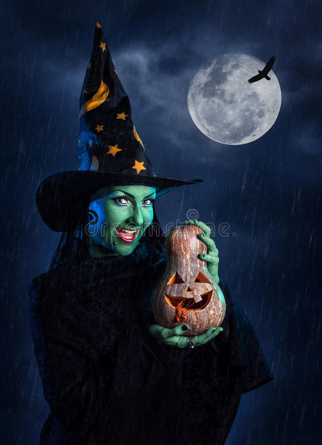 Green witch with pumpkin. Witch with green skin holding carved Halloween pumpkin at moon and dark sky with rain stock photo