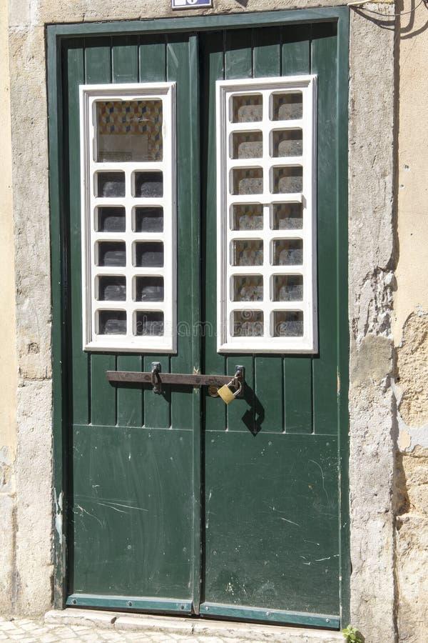 Green woden door with metal lock. Green woden door with windows and a padlock stock image