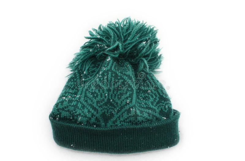 Green wollen hat in the snow stock images