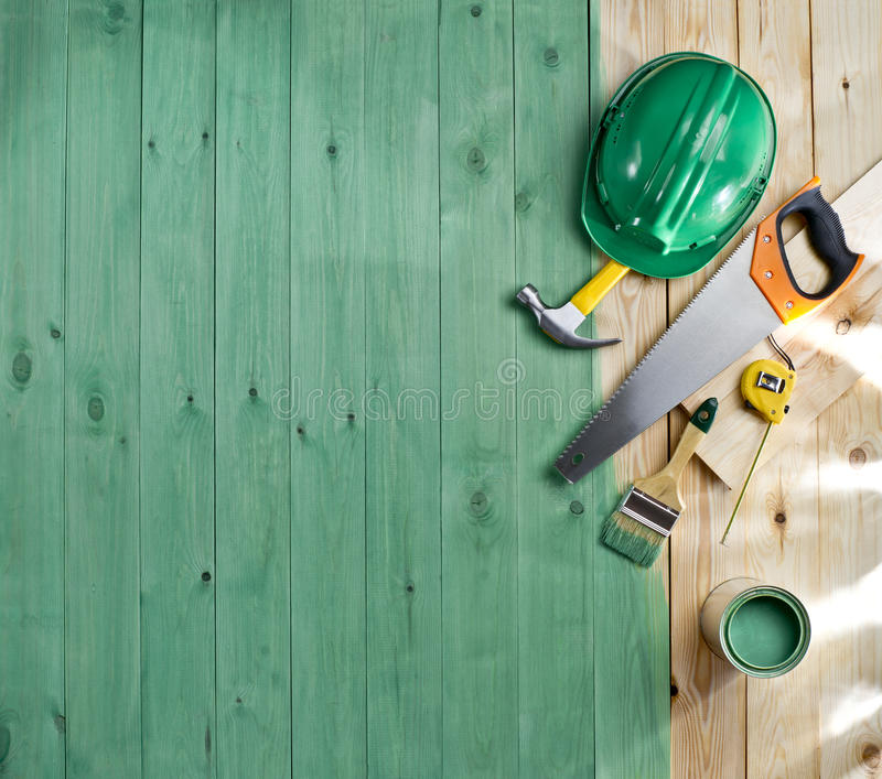Green wood floor with a brush, paint, tools and helmet. Green wood texture floor with a brush, paint, tools and helmet stock photo