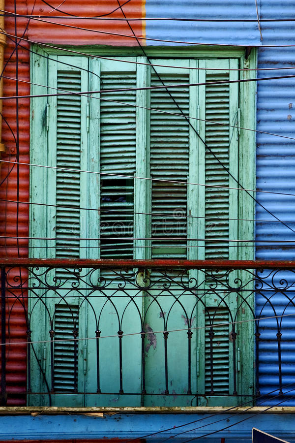 Green wood venetian blind and a red blue wall royalty free stock photos