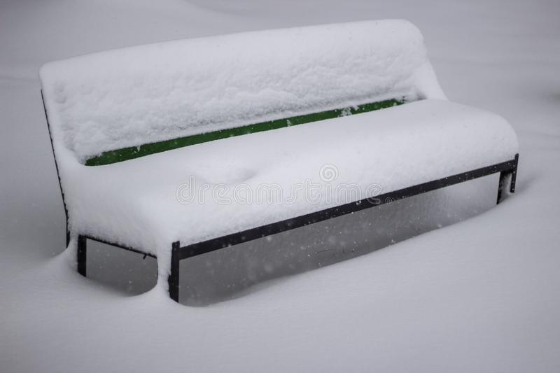 Green wooden bench with show on white background at moment of snowfall and blizzard royalty free stock photography