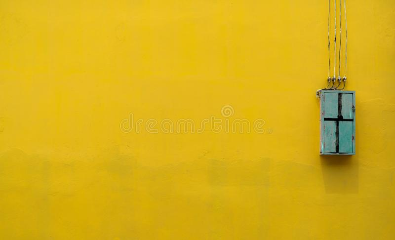 Green wooden box, electric control equipment in the factory on yellow vintage concrete wall background with copy space. Safety. In home and factory industrial stock photo