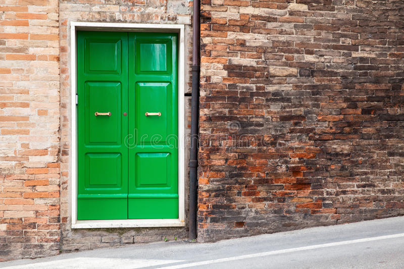 Green wooden door in old brick wall royalty free stock photos