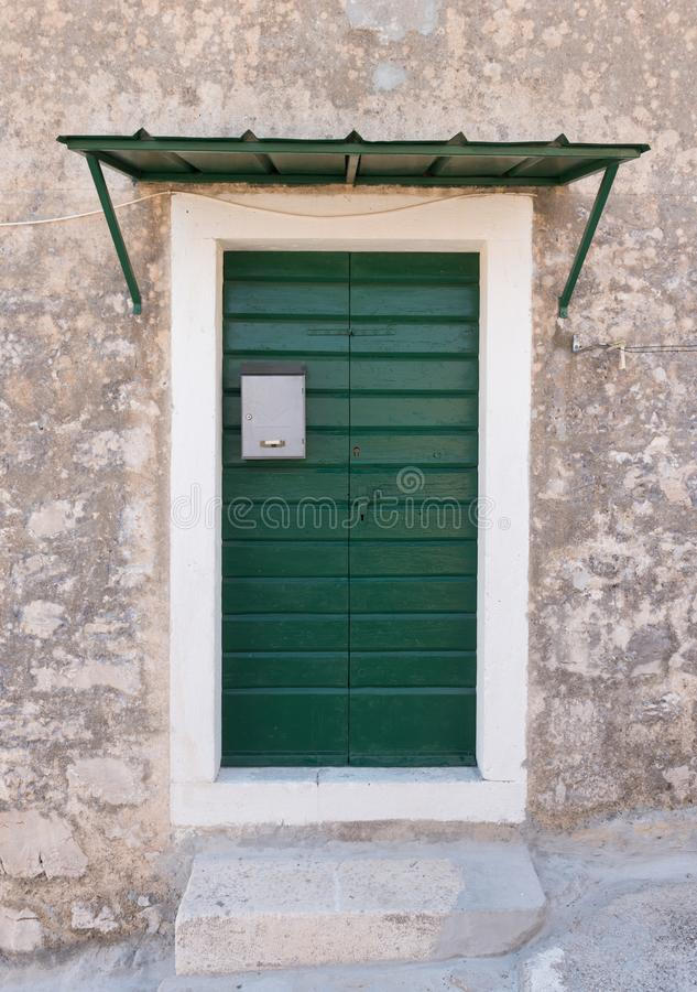 Green wooden doors with silver mailbox on a stone house. Exterior architectural details. royalty free stock photos
