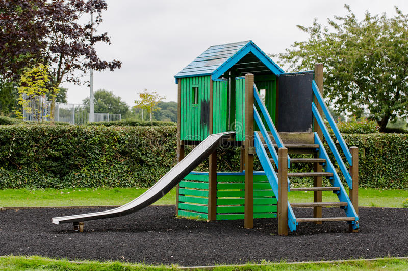Green wooden house with slider on empty playground royalty free stock photo