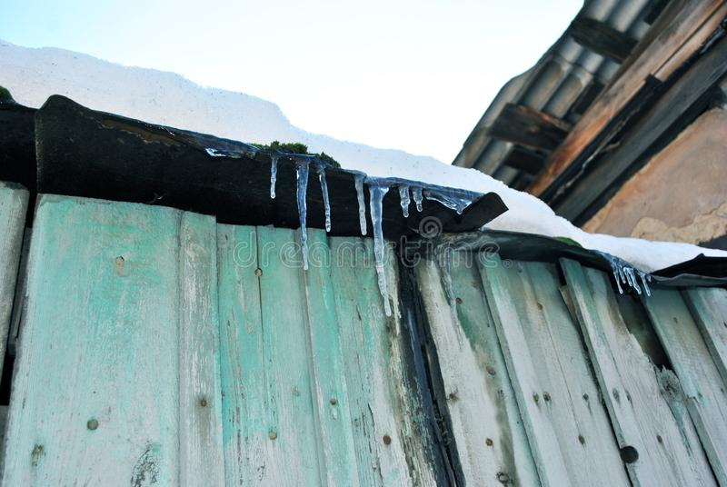 Green wooden old wall with dark shabby roof with icicles and white snow on top, view from ground on blue clear sky background royalty free stock images