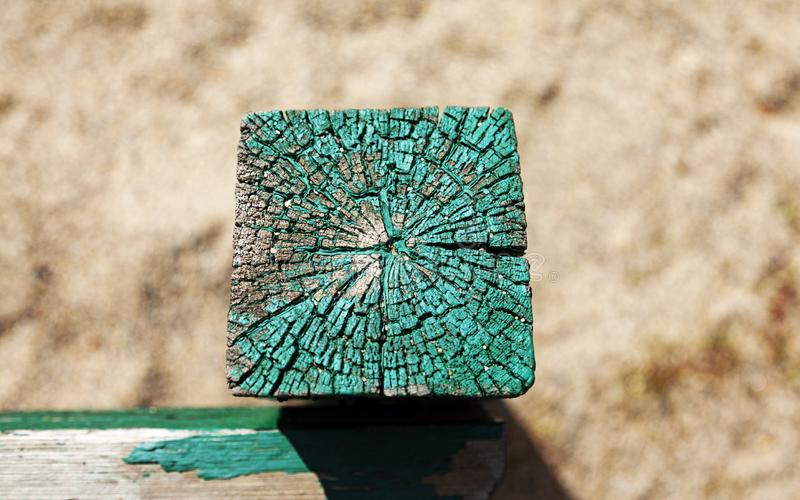 Green wooden post in sandbox as seen from above stock image