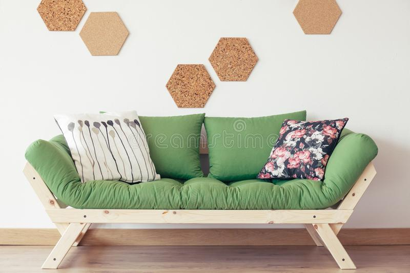 Green wooden sofa. Floral patterned pillow on green wooden sofa against white wall with natural cork royalty free stock photos