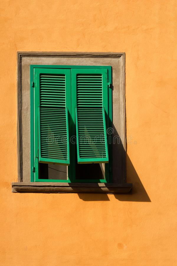 Green wooden window with shutters on the yellow wall. Latticed wooden window with open shutters and shadow on sunny day on yellow wall royalty free stock photos