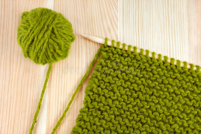 Green wool and garter stitch on knitting needle. Green ball of wool and garter stitch on a knitting needle, on wooden table stock photos