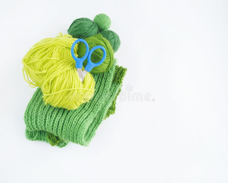 Green woolen threads. Tangles of thread,scissors and a knitted scarf. The view from the top. Needlework handmade. royalty free stock photos