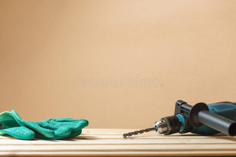 Green working gloves with hammer drill on lining wooden table and copy space background. Protection workers concept. Green working gloves with green drill on royalty free stock images