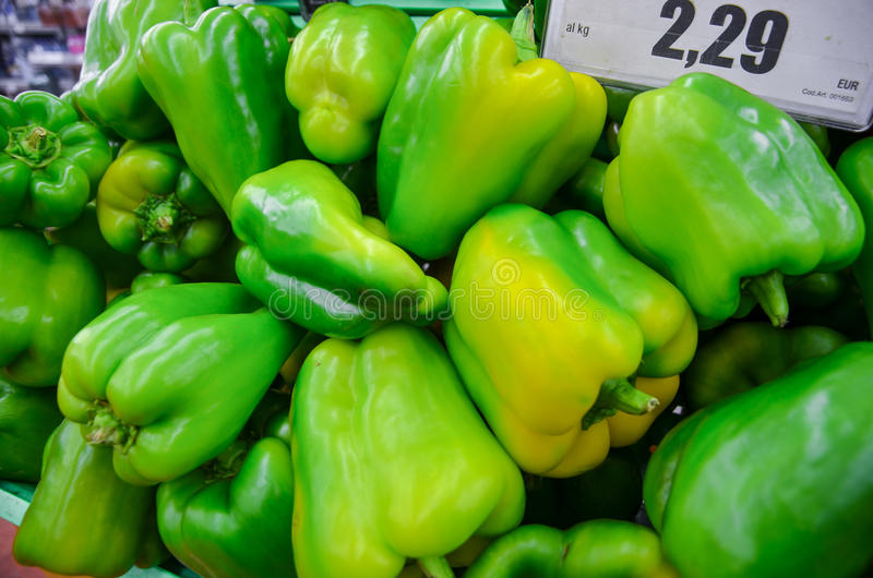 Green yellow bellpeppers at the market with price tag royalty free stock images