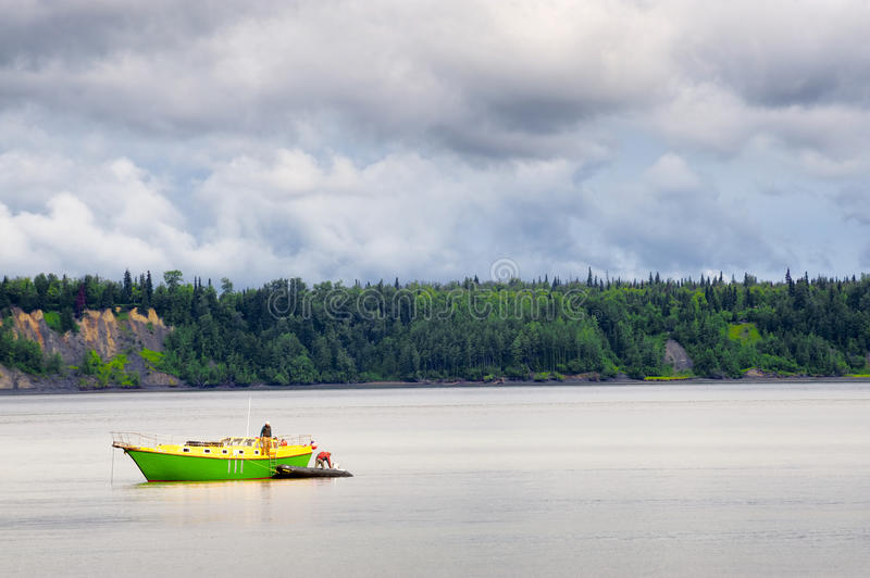 Green and Yellow boat in Cook Inlet, Alaska royalty free stock photography