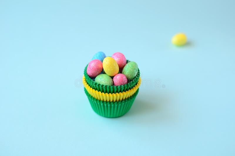 Green and yellow cupcake baking mold with colorful shiny eggs on blue background royalty free stock images