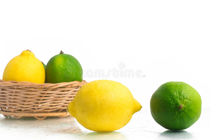 Green and Yellow Lemon or Lime. Green and Yellow Lemon or Lime over a wet white background royalty free stock image