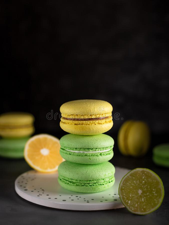 Green and yellow macarons. close-up. dark background. Green and yellow macarons, lemon, lime. close-up. dark background. delicious french dessert royalty free stock image