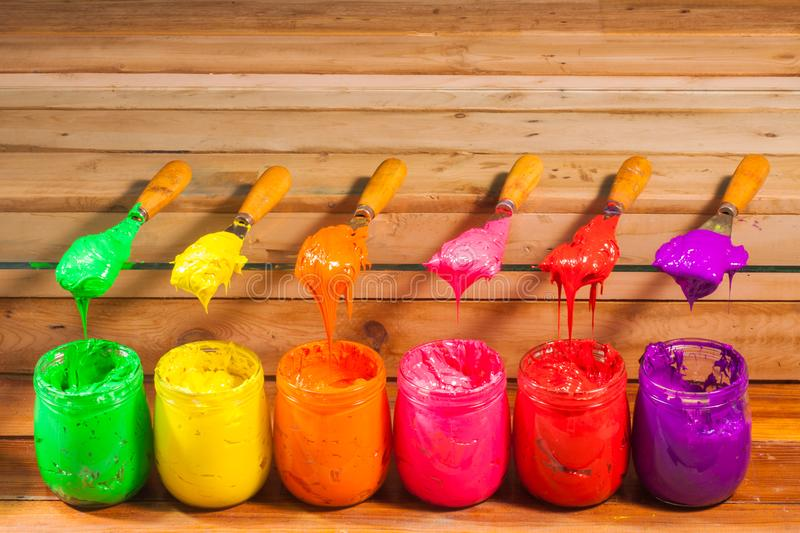 Green yellow orange pink red and purple colors of plastisol ink. In tee shirt factory with coppy space stock photo
