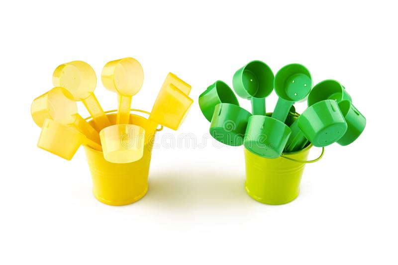 Green and yellow plastic spoons in small buckets. on white background.  stock images