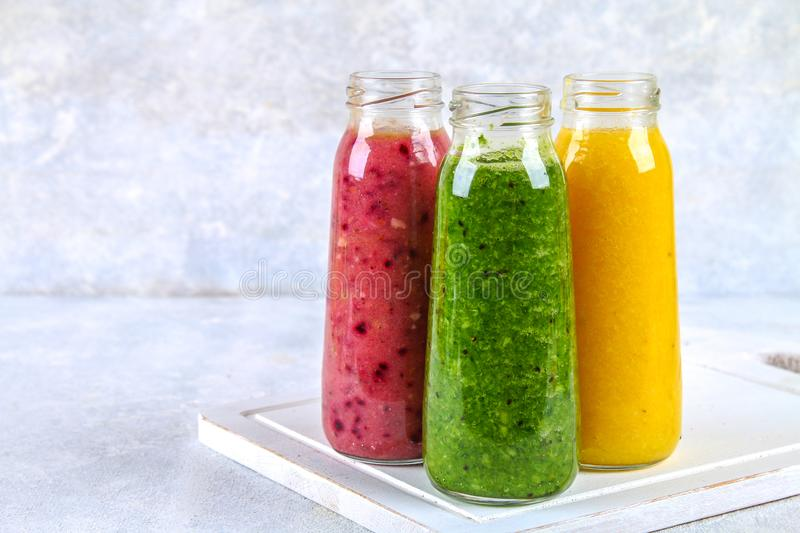 Green, yellow, purple smoothies in bottles of berries, greens, oranges on a white board on a gray table. Green, yellow, purple smoothies in bottles of berries stock image
