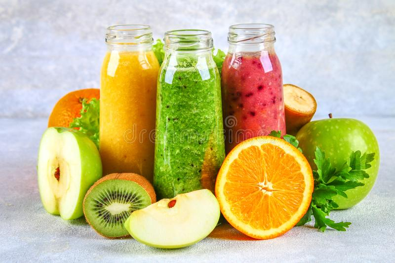Green, yellow, purple smoothies in currant bottles, parsley, app royalty free stock photos
