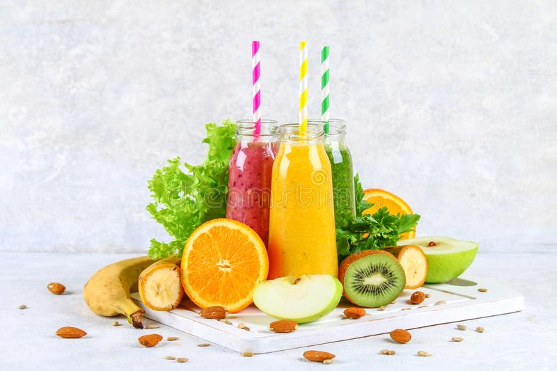 Green, yellow, purple smoothies in currant bottles, parsley, app royalty free stock images